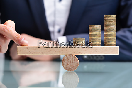 businessperson balancing increasing stacked coins with