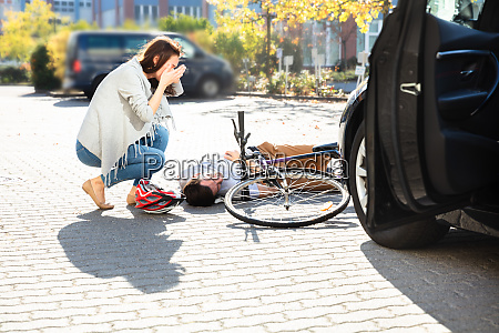 frau schaut bewusstlosen maennlichen radfahrer liegen
