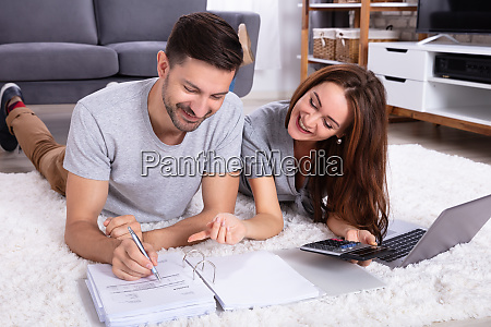 couple calculating invoice with calculator