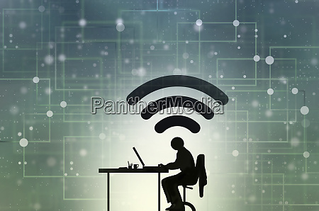 man working at desk connected to