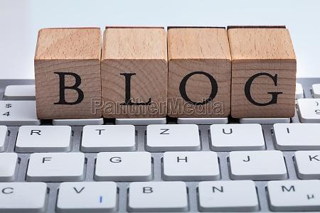 blog text auf holzblock ueber tastatur