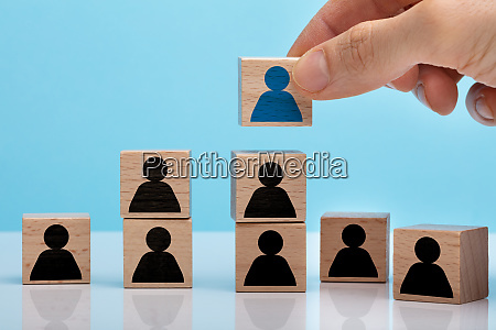 hand stacking wooden block with people