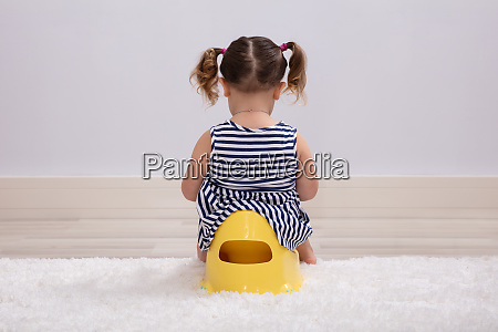 female toddler sitting on a potty