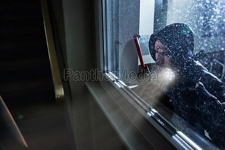 einbrecher schaut in ein hausfenster