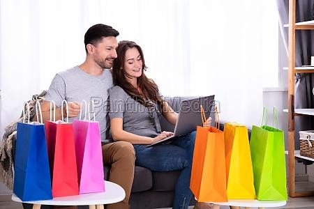 froehliches jungpaar shopping auf dem laptop
