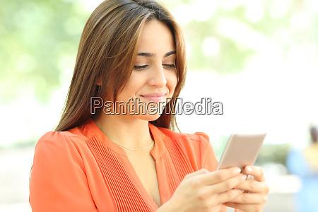 teen in orange verwendet smartphone zu