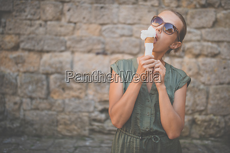 woman eating ice cream outside on