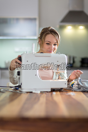 pretty young woman sewing clothes with