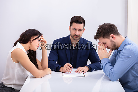 depressed couple sitting in front of
