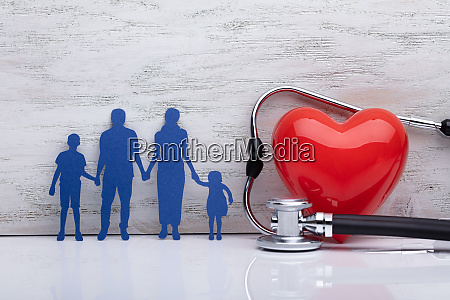 family holding hands beside heart shape