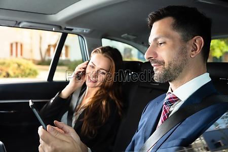 geschaeftsfrau sitzt im innenwagen neben ihrer