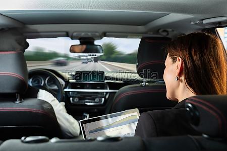 geschaeftsfrau sitzt im innenwagen auf grafik