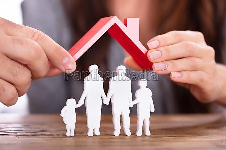 paar schuetzt familienfiguren mit dach