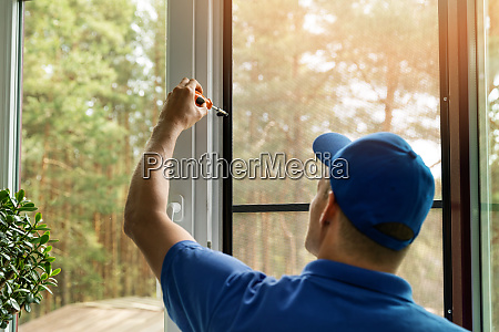 man installing mosquito net wire screen