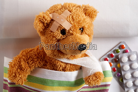 injured teddy bear with arm in