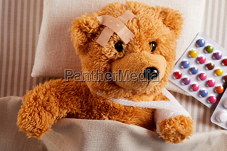 little injured teddy bear lying sick