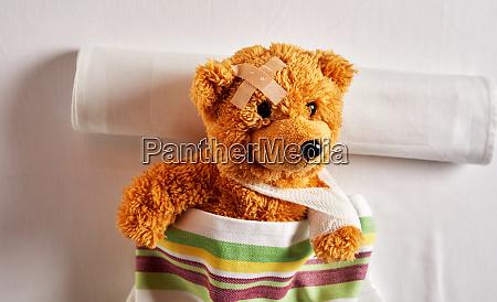 little brown teddy bear lying in