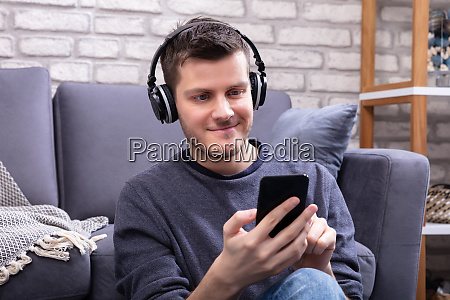 mann hoert musik mit kopfhoerern