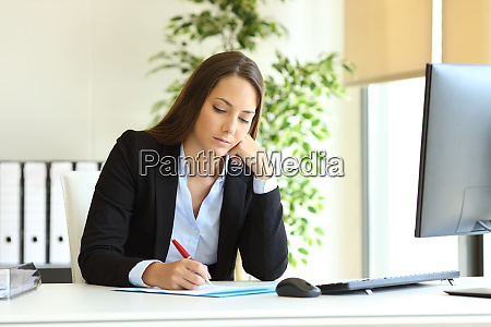 serious office worker writing on document
