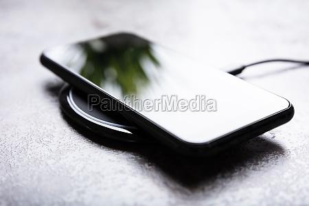 drahtloses ladepad und smartphone am schreibtisch