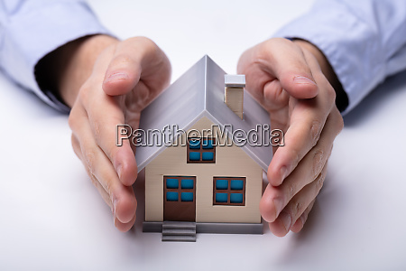 mans hand protecting model house