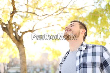 happy man relaxing breathing deep fresh