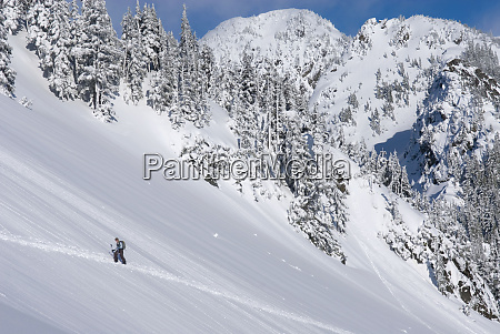 snowshoer walking up snowy hillside