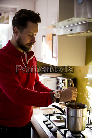 man standing in a domestic kitchen
