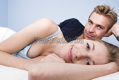 caucasian couple hugging in bed
