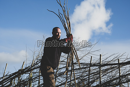 bearded man holding bunch of wooden