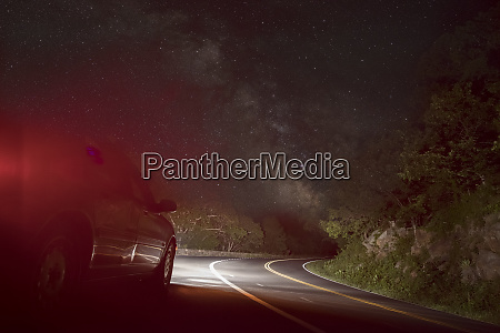 car on winding road under starry