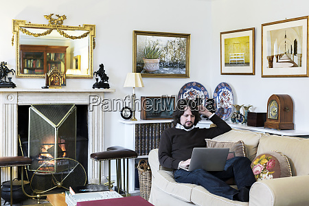caucasian man sitting on sofa using