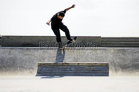 caucasian man riding skateboard in skate