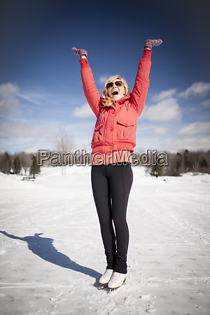 caucasian woman on ice skates cheering