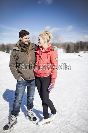 caucasian couple ice skating on frozen