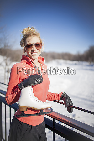 caucasian woman carrying ice skates in
