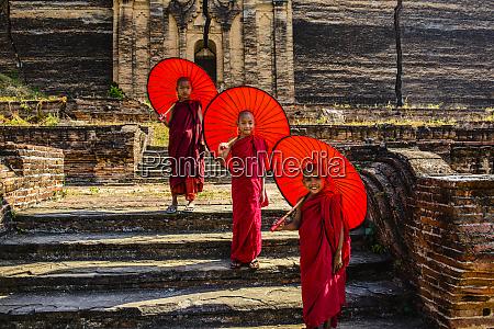 asiatische moenche stehen unter regenschirmen in