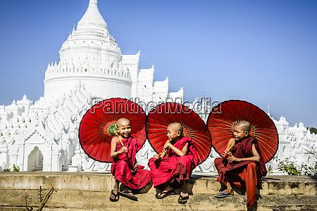 asiatische moenche sitzen unter regenschirmen in