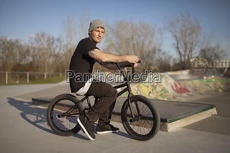 caucasian man riding bmx bicycle at
