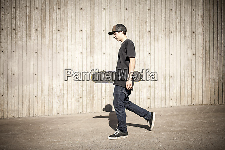 caucasian man carrying skateboard near wooden