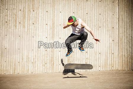 caucasian man doing skate trick near