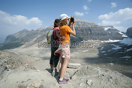 caucasian mother and daughter photographing scenic