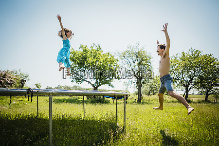 playful father and daughter jumping on