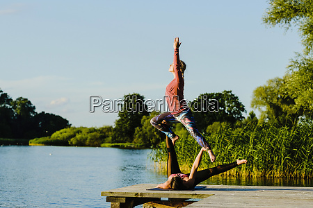 women practicing acroyoga on sunny lakeside