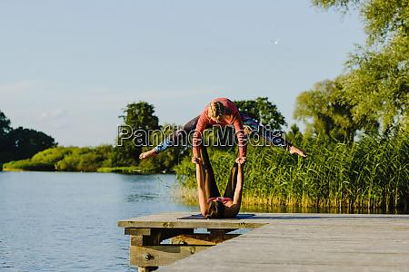 women practicing acro yoga on sunny