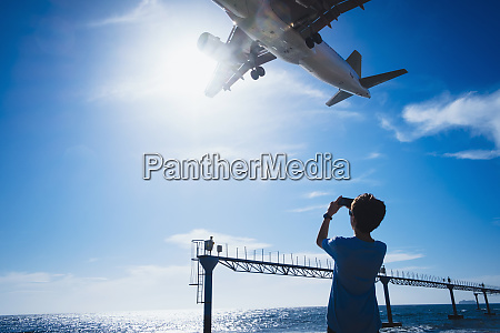 boy with camera phone photographing airplane
