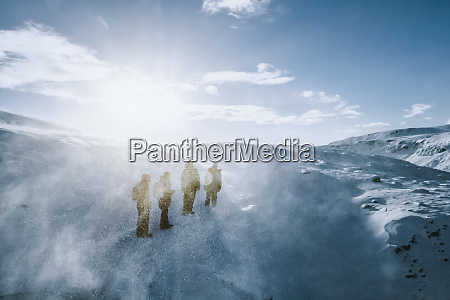 people walking along sunny windy snow