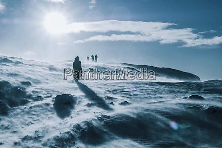 people walking across sunny windy snow