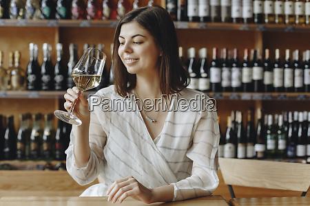 laechelnde junge frau haelt glas von