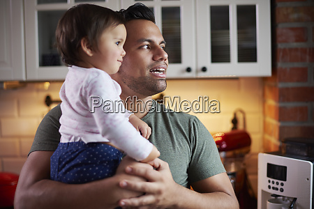father holding baby girl in kitchen